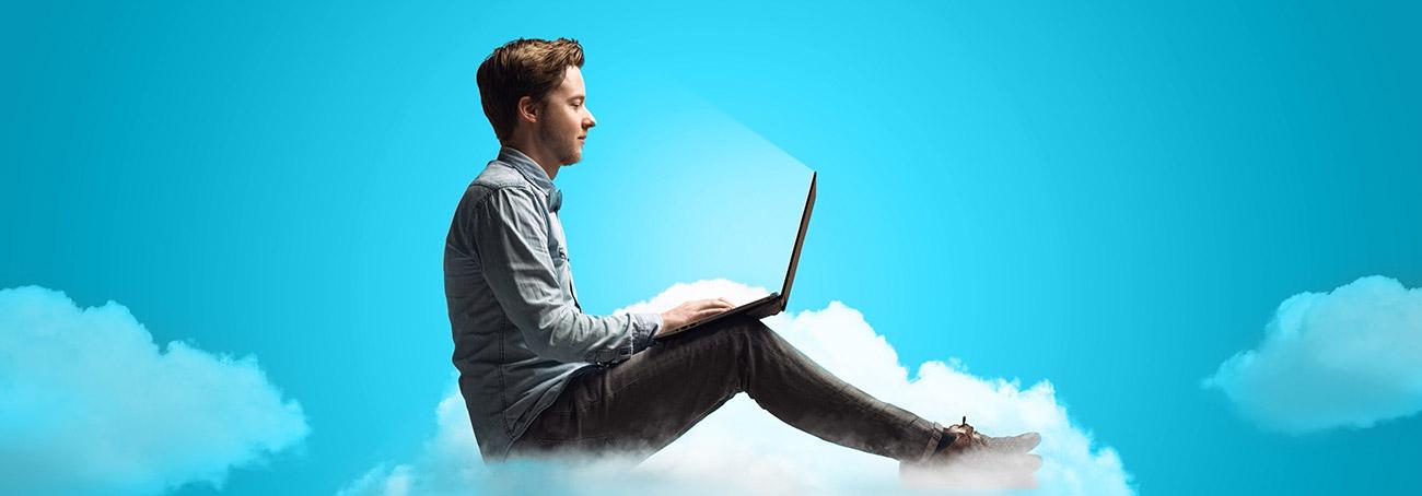 Mann mit Laptop auf Cloud